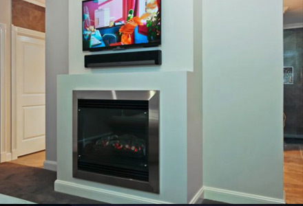 Wall-mounted TV and Sonos Playbar mounted above a gas fireplace.